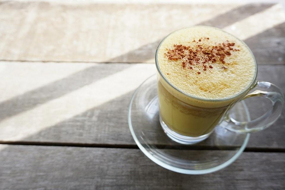Eine Tasse mit goldener Milch und Schaum - eine gute Routine am Morgen.
