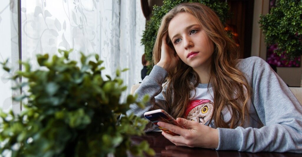 Mädchen am Fenster mit Handy